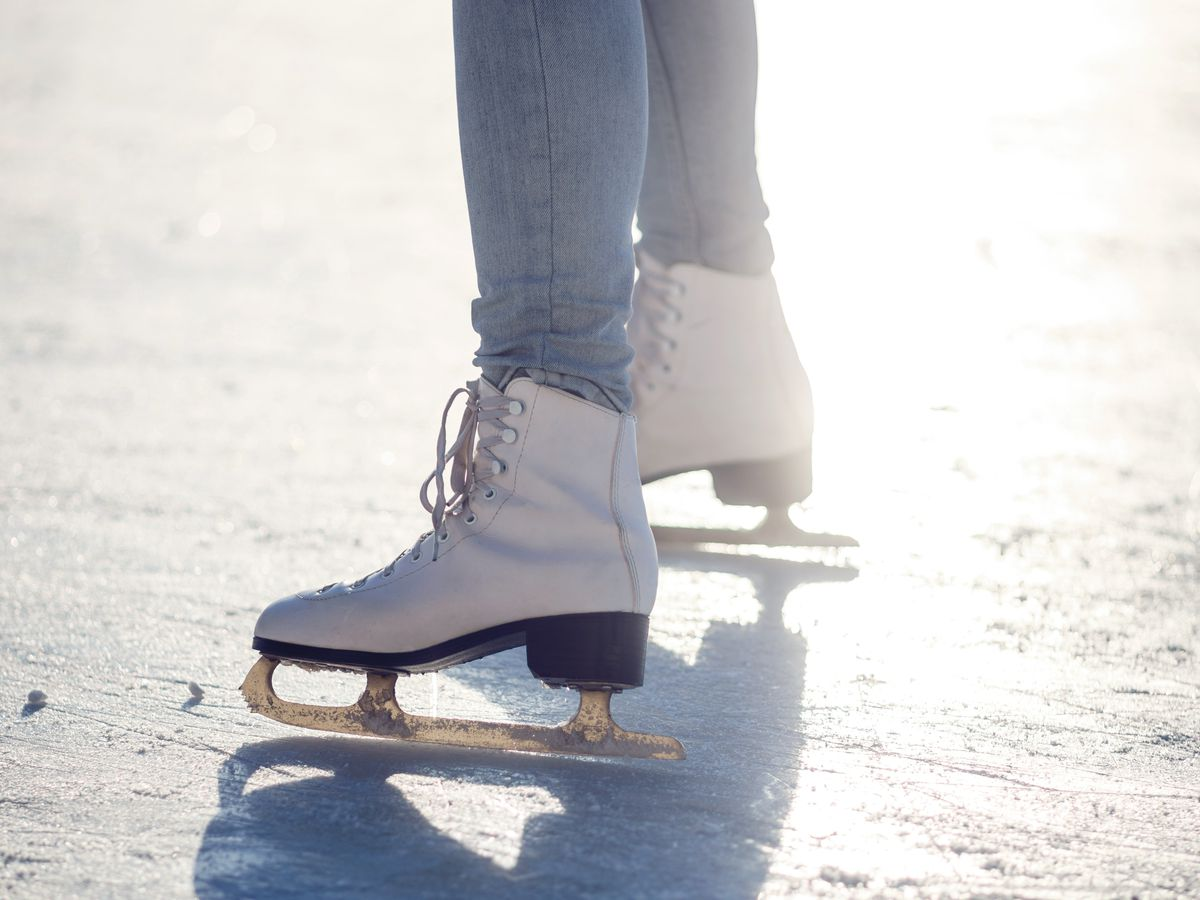 A person's legs are shown ice skating.