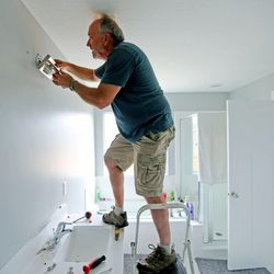 Steve Allen works to install a new light fixture in the master bath as he and his wife, Michelle, work to unpack their belongings Wednesday, May 20, 2015, and move into their new home in Heber.