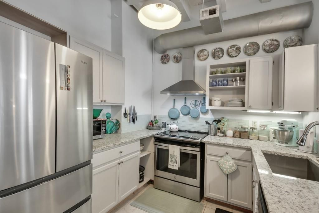 A white kitchen with an exposed ductwork.
