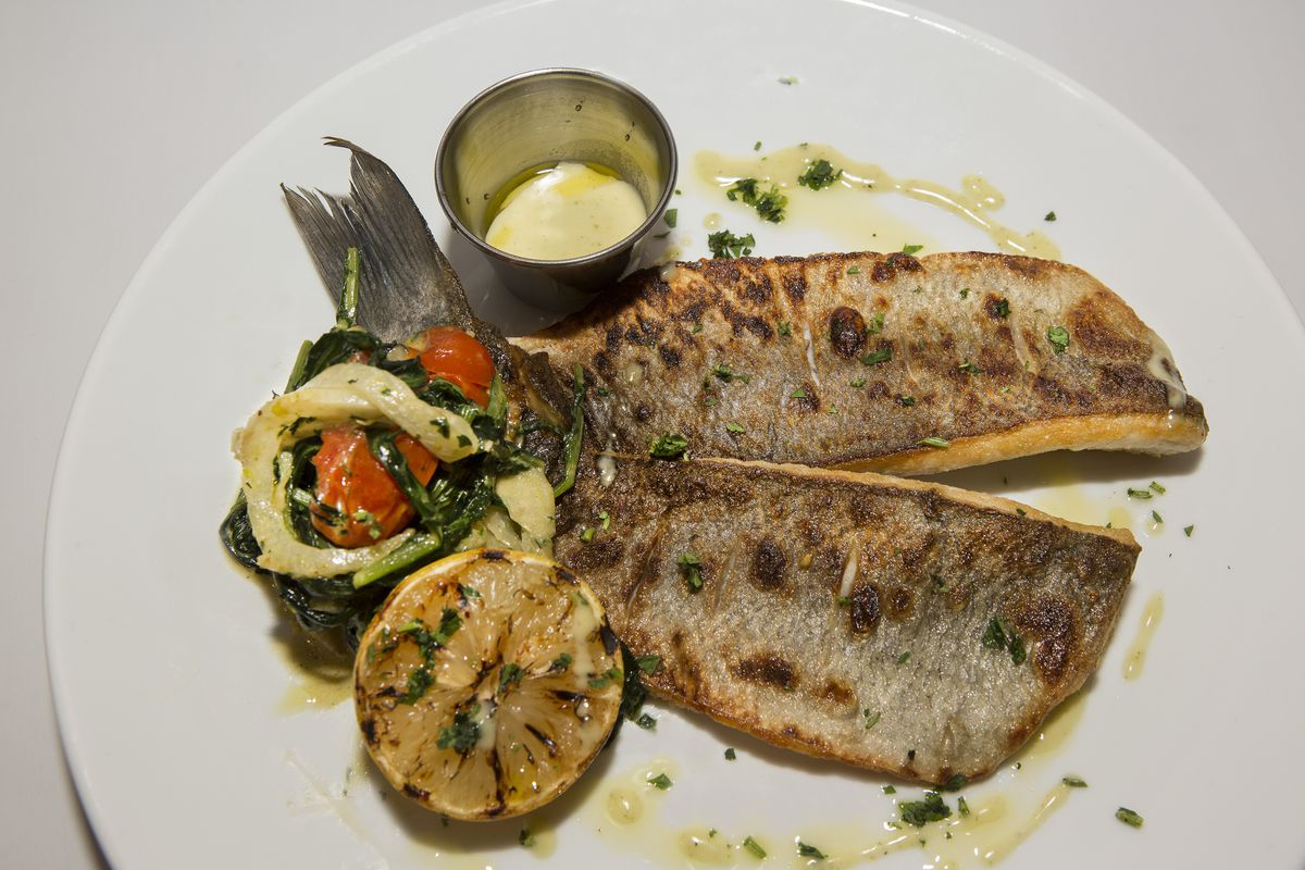 A grilled fish with lemon and veggies.