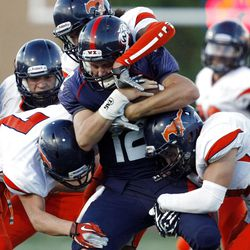 Woods Cross #12 Skyler Farnes, center, is tacked by a host of Mountain Crest players Friday, Aug. 31, 2012.
