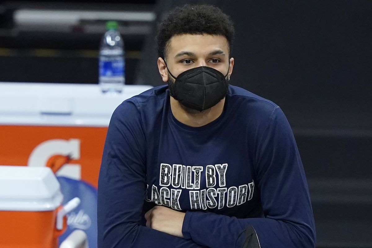 Jamal Murray of the Denver Nuggets looks on from the bench against the Sacramento Kings during the first half of an NBA basketball game at Golden 1 Center on February 06, 2021 in Sacramento, California.