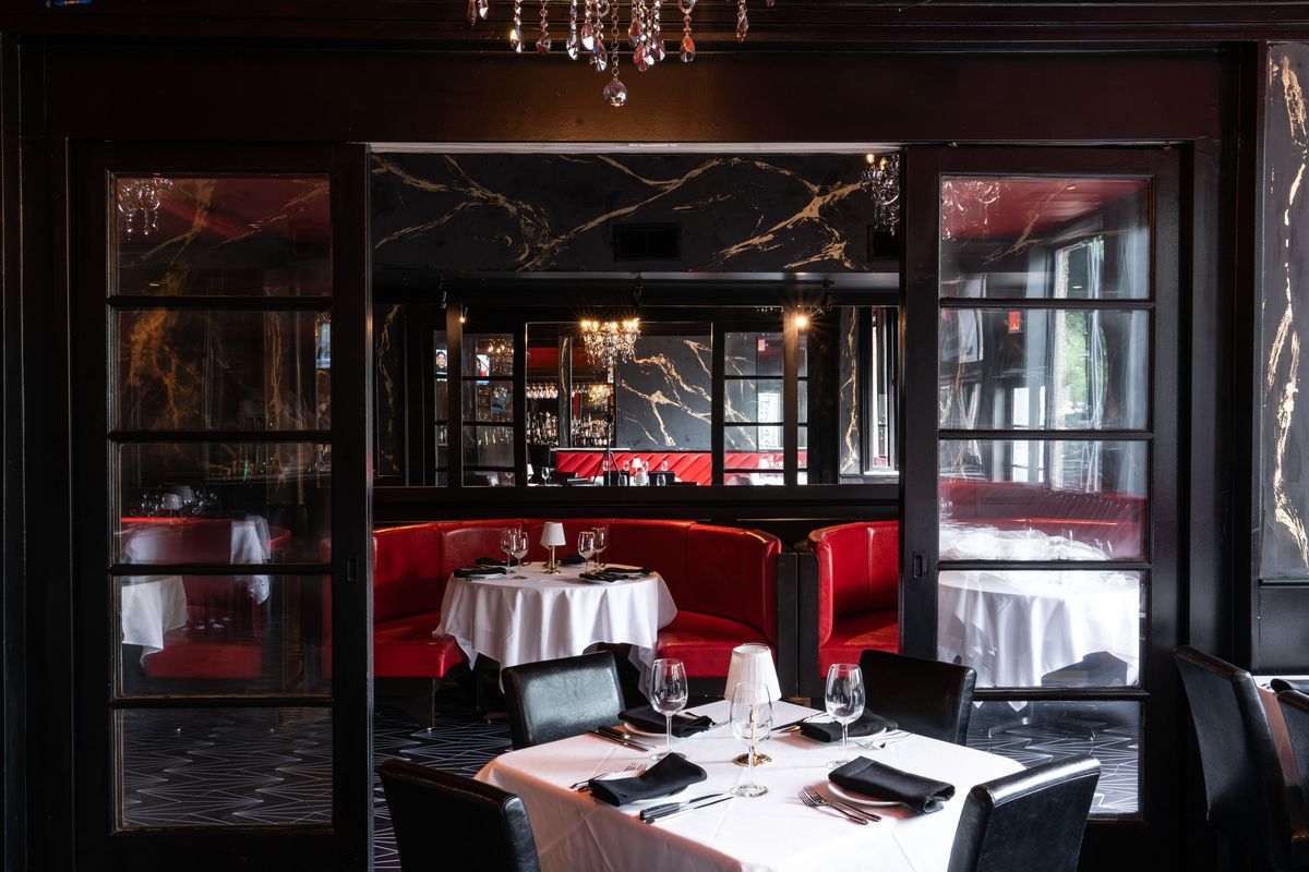 a dining room with white table cloths, red leather booths and black and gold marbeled walls