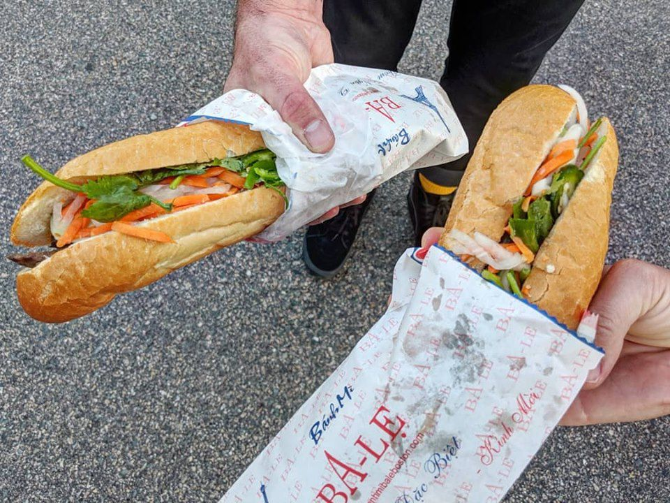 Hands hold two banh mi over pavement