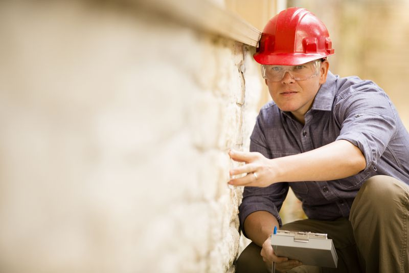 Engineer examines a building/home exterior wall. He wears a red hard hat and clear safety glasses and holds a clipboard.