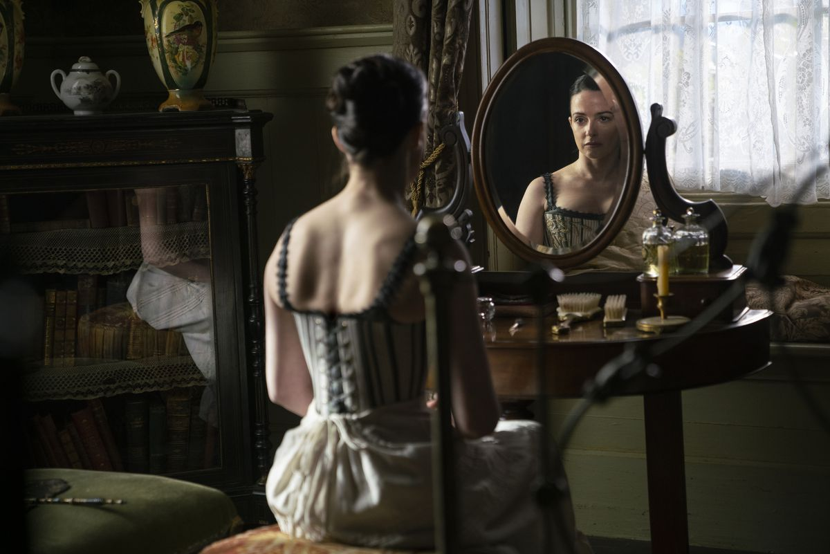 Laura Donnelly, in a corset and underskirt, looks in a mirror in The Nevers