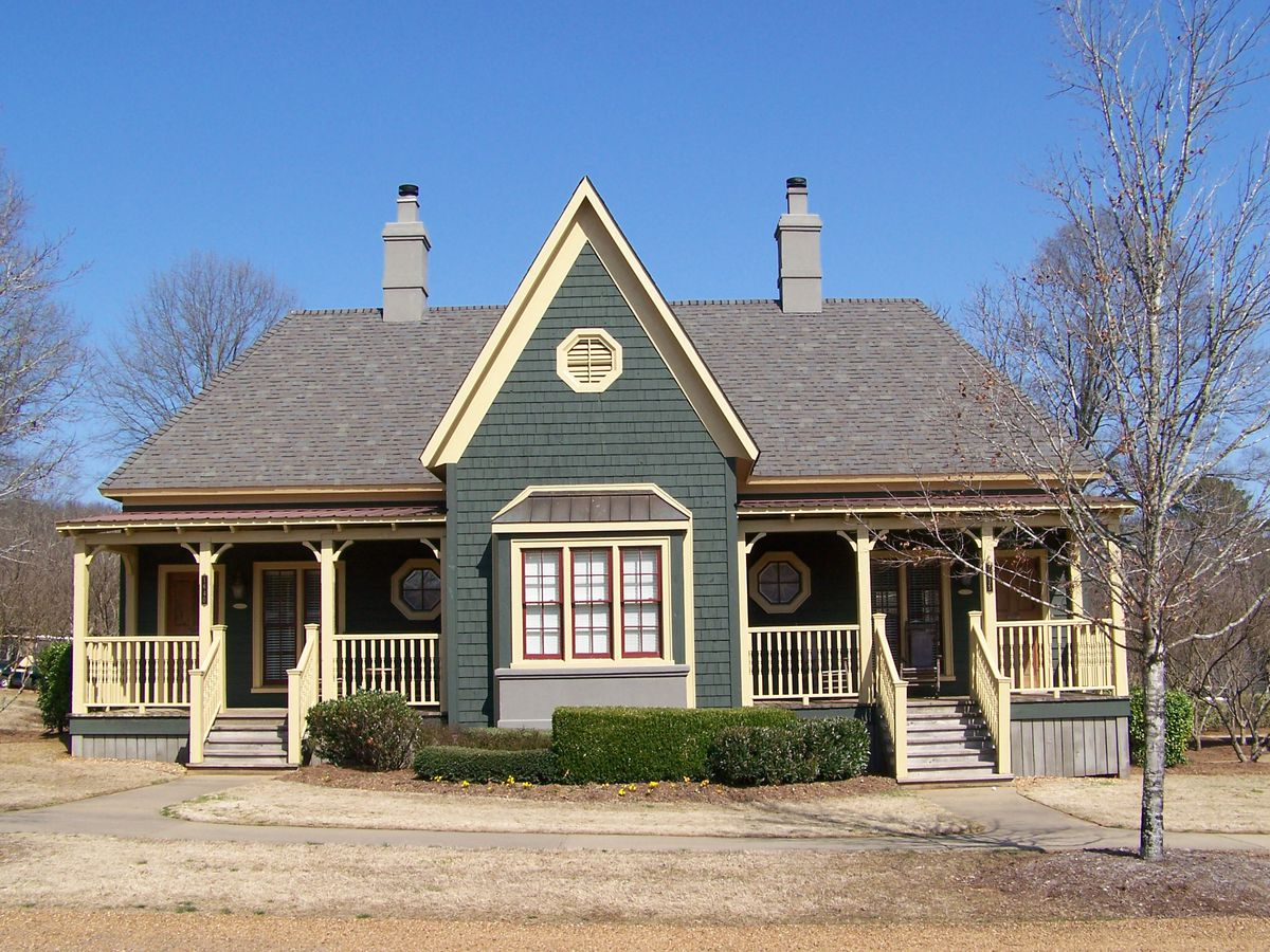 The exterior of a cottage. The facade is green with a brown roof.