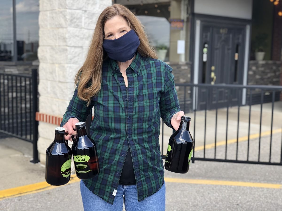 A woman with long hair and a facemask delivers curbside growlers.