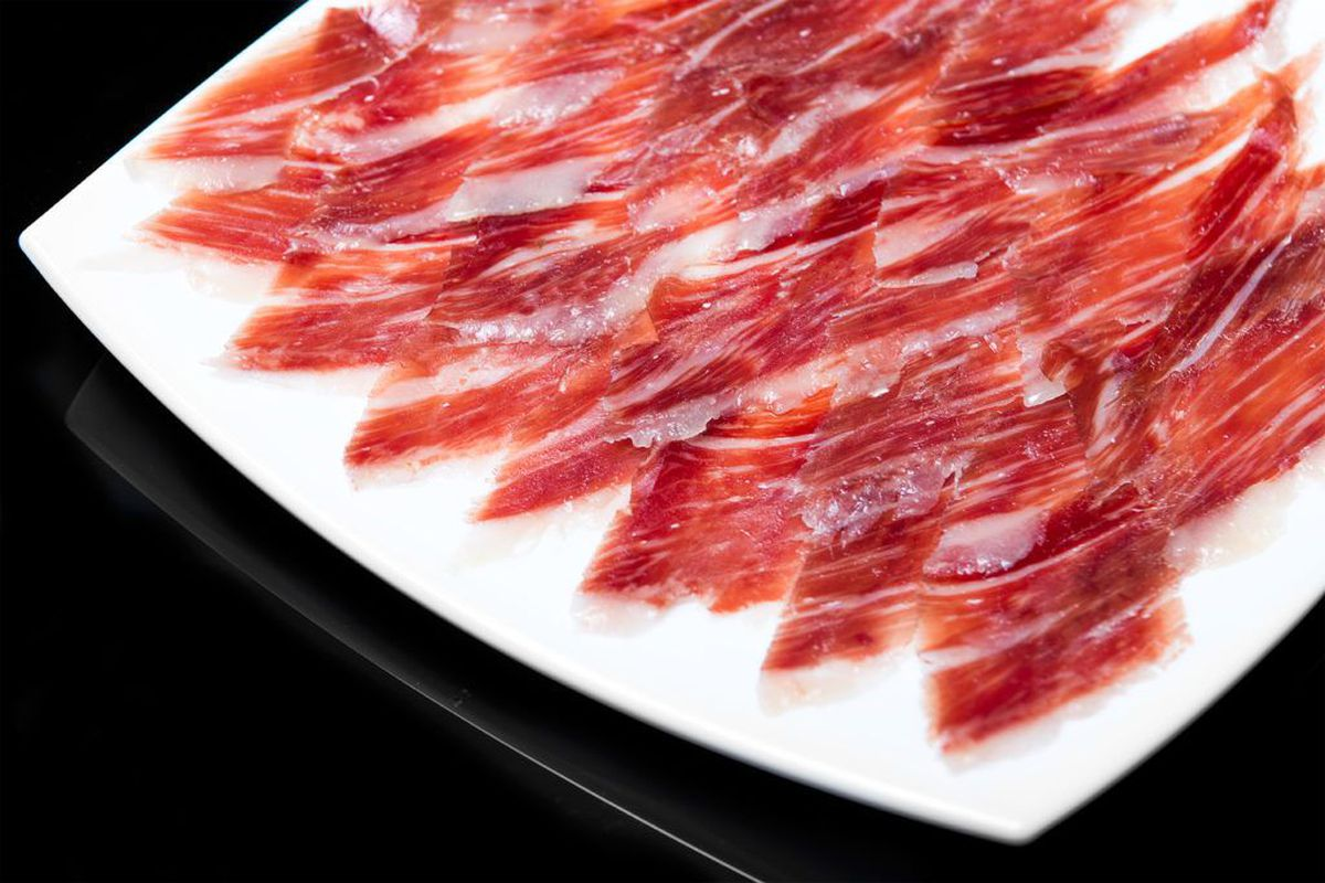 Thin slices of Jamon Iberico on a white plate