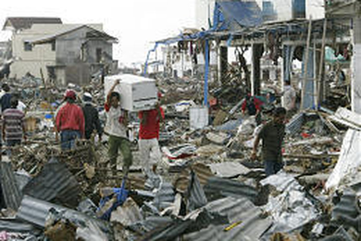 Tsunami survivors, seen in 2004, carry items from the rubble at a commercial area of Banda Aceh, Indonesia.