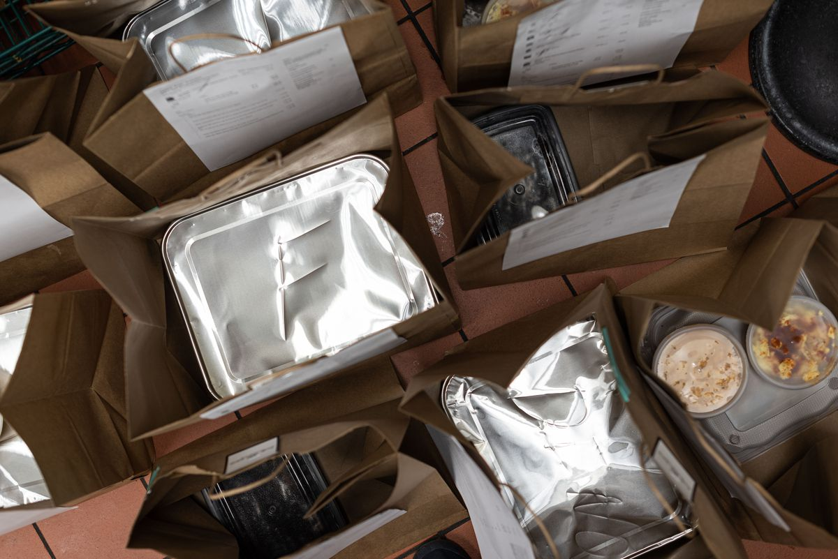 An overhead look at paper bags and tins of food ready to go.