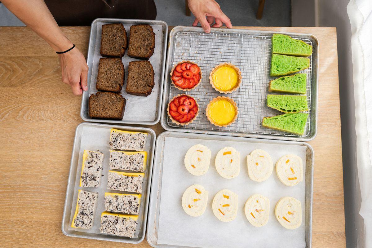 Hands hold baking sheets full of yellow and red tarts, bright green spongecake, mango roll cakes at Berlu's bakery