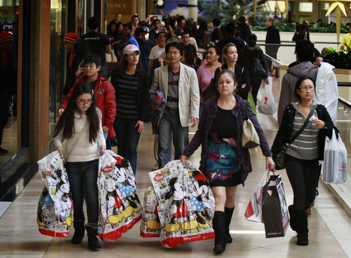 Shoppers in a mall carrying large Disney store bags.