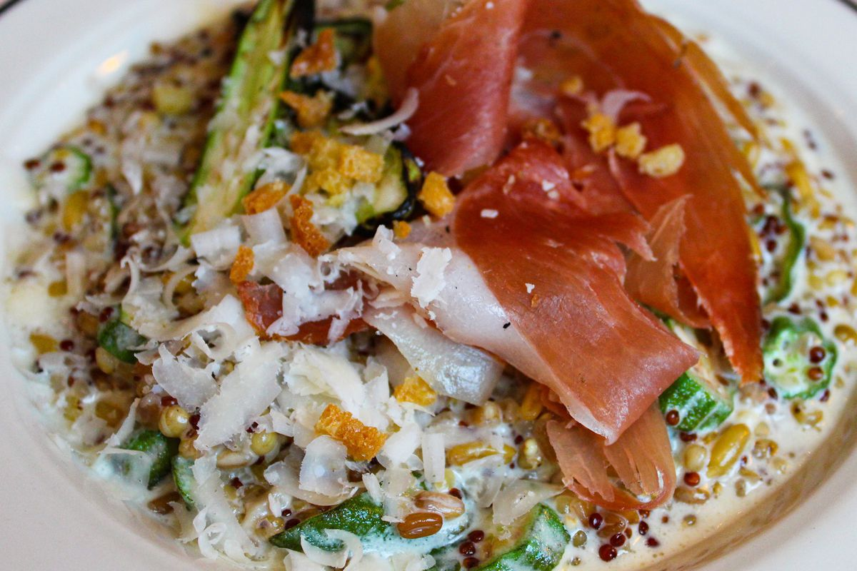 a plate of risotto topped with cured meat