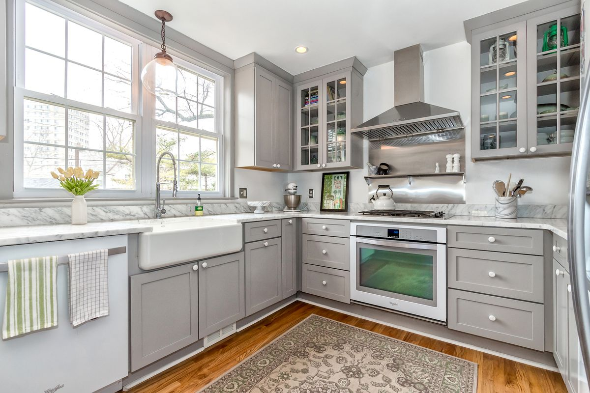 The kitchen has gray cabinets and two big windows above the white kitchen sink.