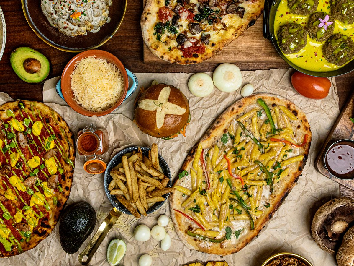 Flatbread pizzas, pretzel buns, mushrooms, and more menu items spread out on a table