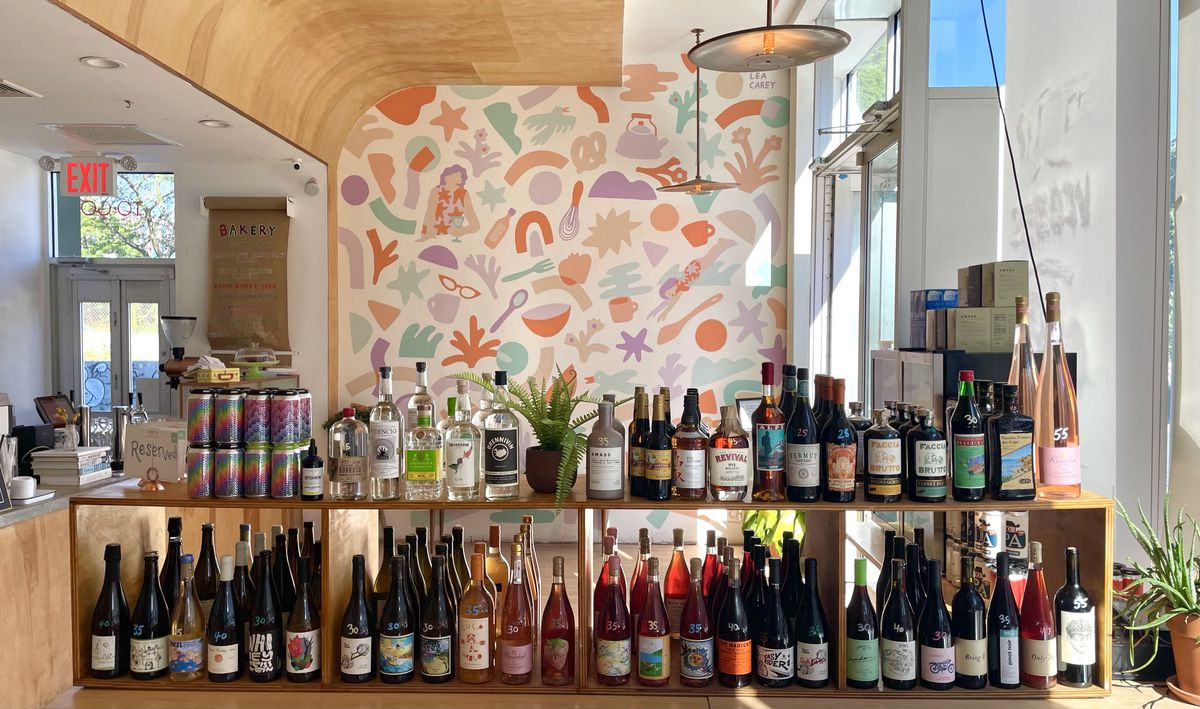A two-tier shelf of wine and liquor sits on display in a well-lit restaurant with colorful wallpaper