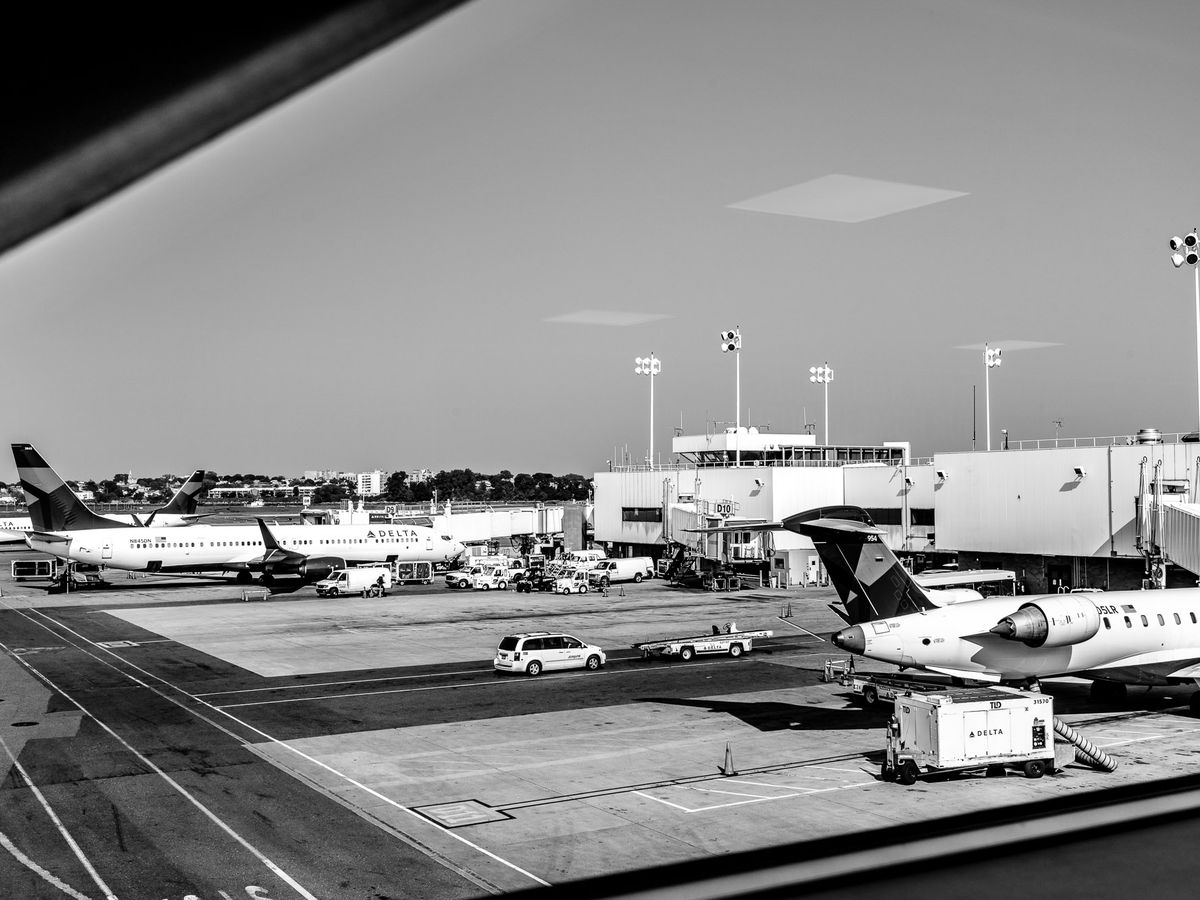 A black and white photo of airplanes on a tarmac.