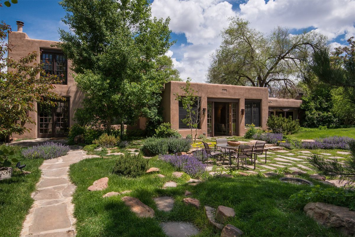 Exterior shot of brown textured adobe house with large windows and French doors, with a landscaped garden in front.