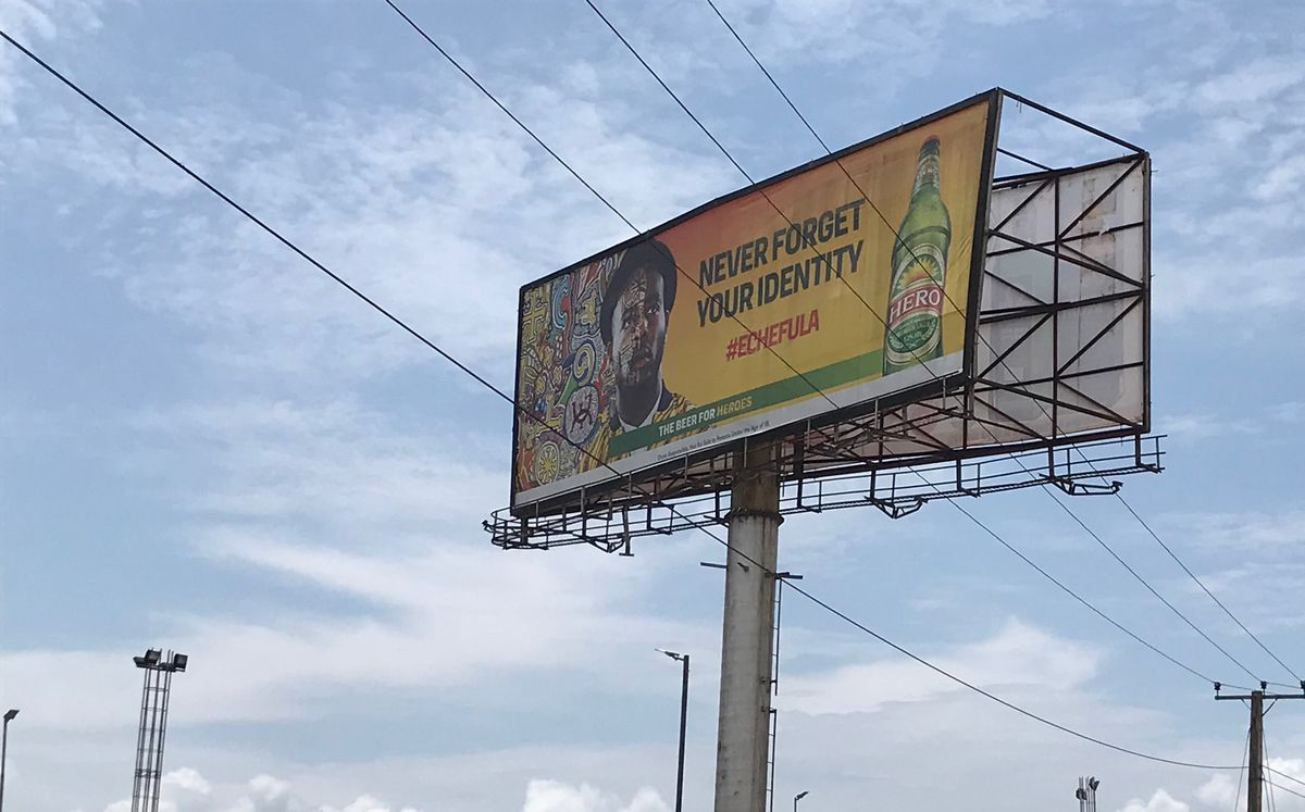 """A billboard reads """"Never forget your identity"""" next to a bottle of Hero lager."""
