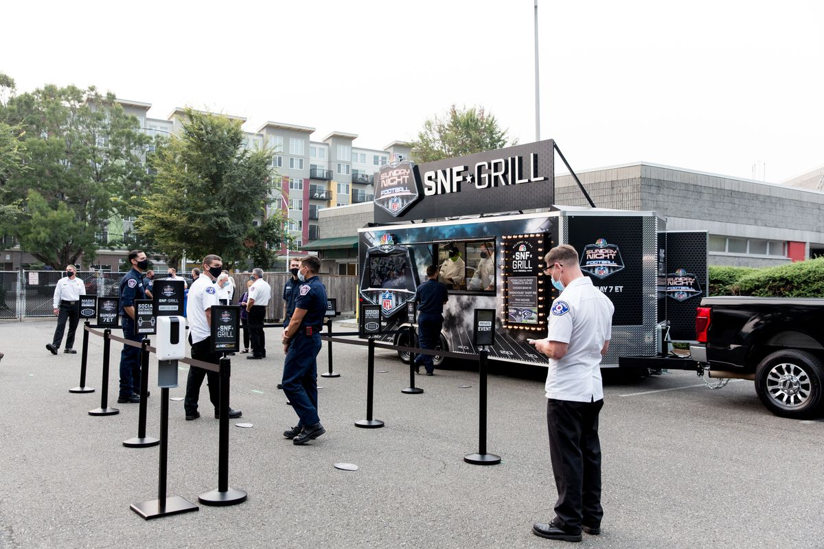 People stand in line to get food from a food truck