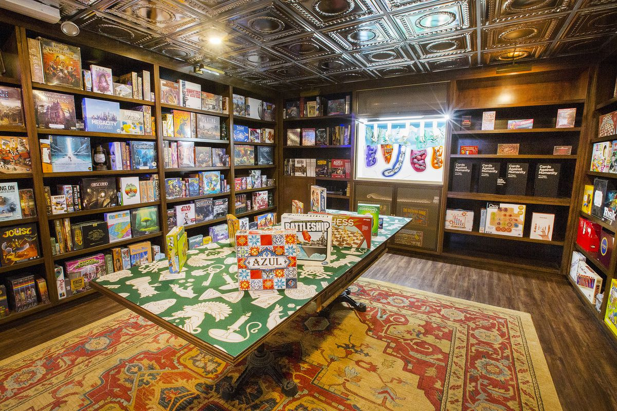 Another view of the inside of the game vault. The top of the tables is covered with a bespoke art print that uses repeating patterns of white game pieces, dice, pawns, and other tokens on a green background. The same pattern serves as the background for its digital marketing materials.