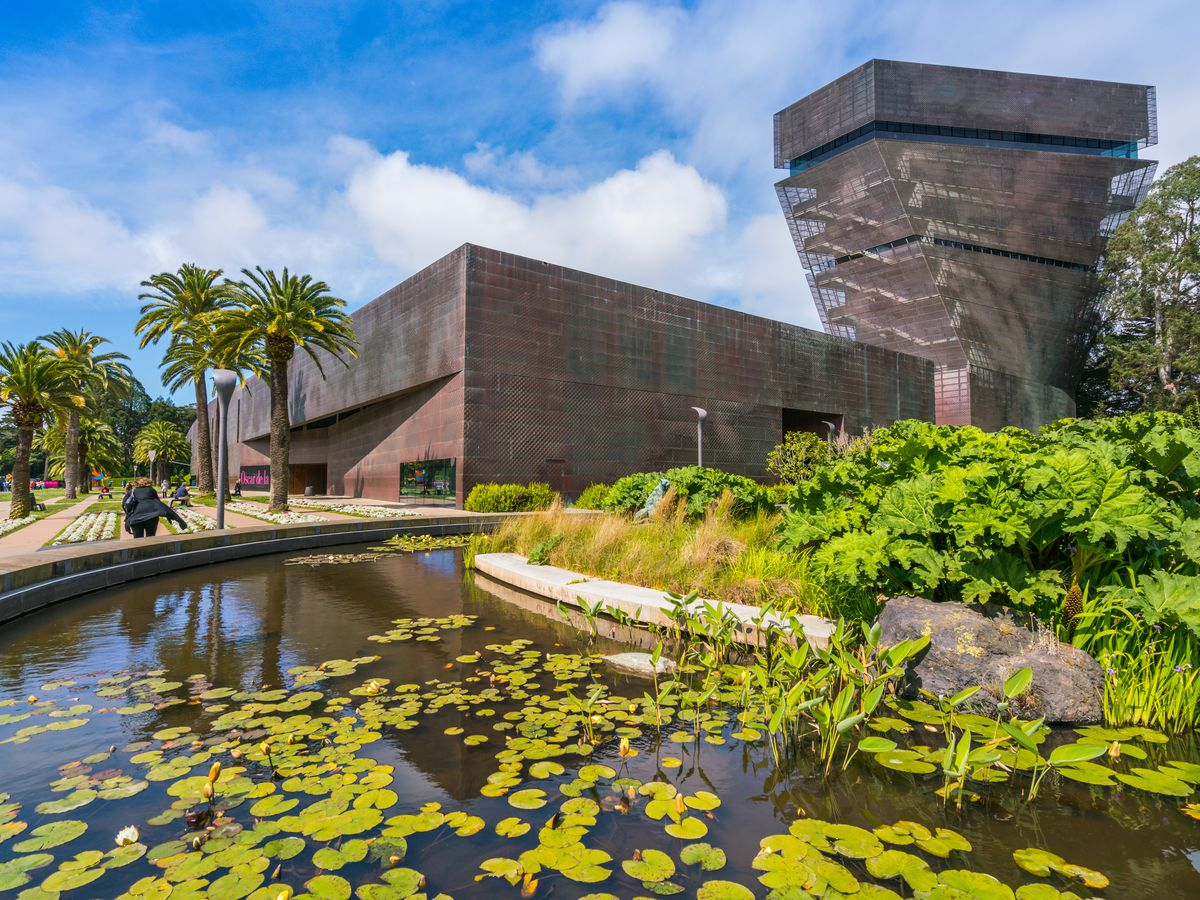 In the foreground is a still water pool with lily pads floating on the surface. In the distance are palm trees and the De Young Museum.