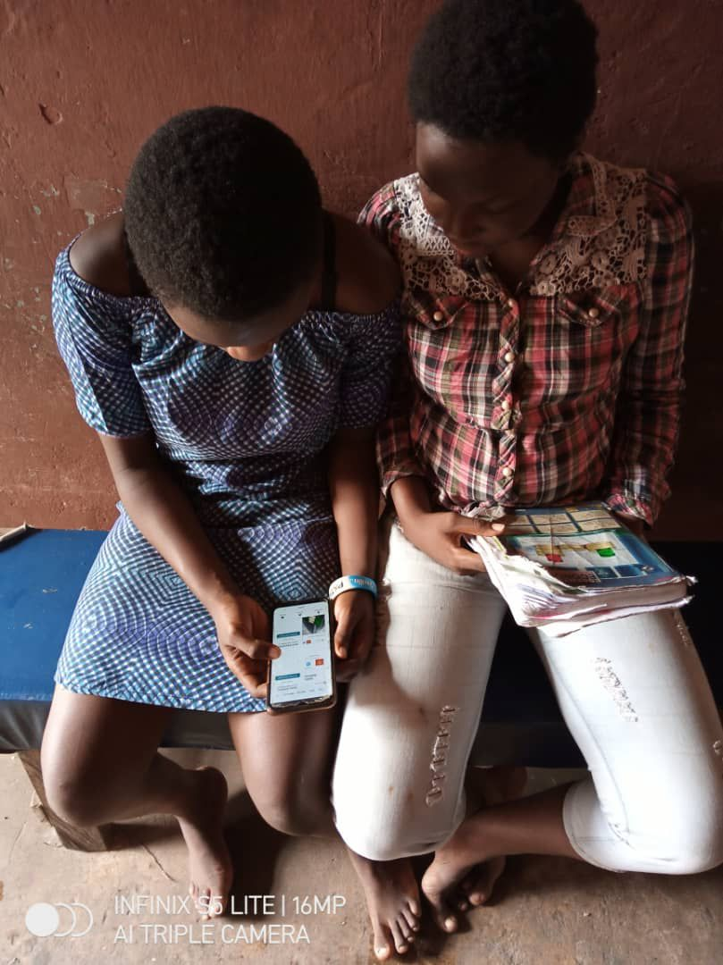 Ifeoluwa Martins (left) and a fellow student use their teacher's mobile phone to look up lessons from the Nigerian secondary school curriculum.