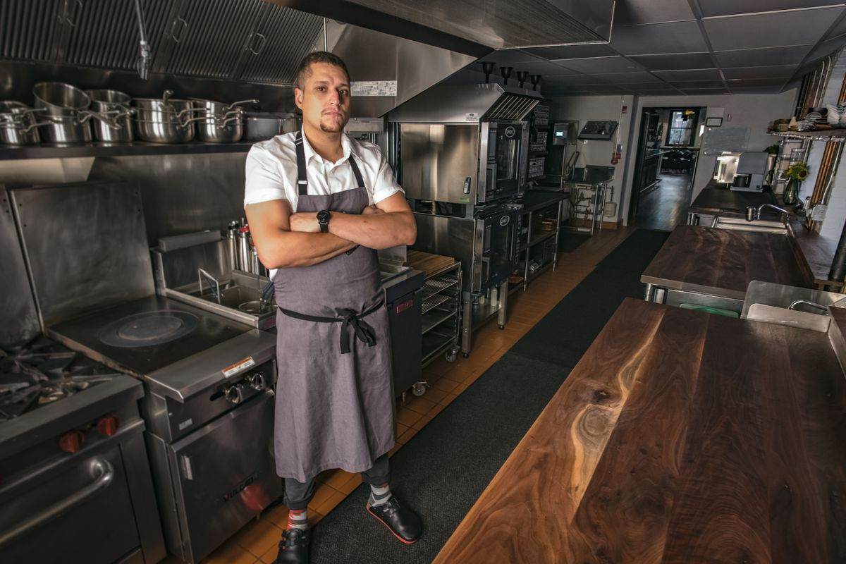 A chef stands with his arms crossed at his chest in a restaurant kitchen.