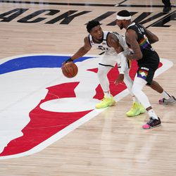 Utah Jazz's Donovan Mitchell (45) works against Denver Nuggets' Torrey Craig (3) during the second half an NBA first round playoff basketball game, Tuesday, Sept. 1, 2020, in Lake Buena Vista, Fla.