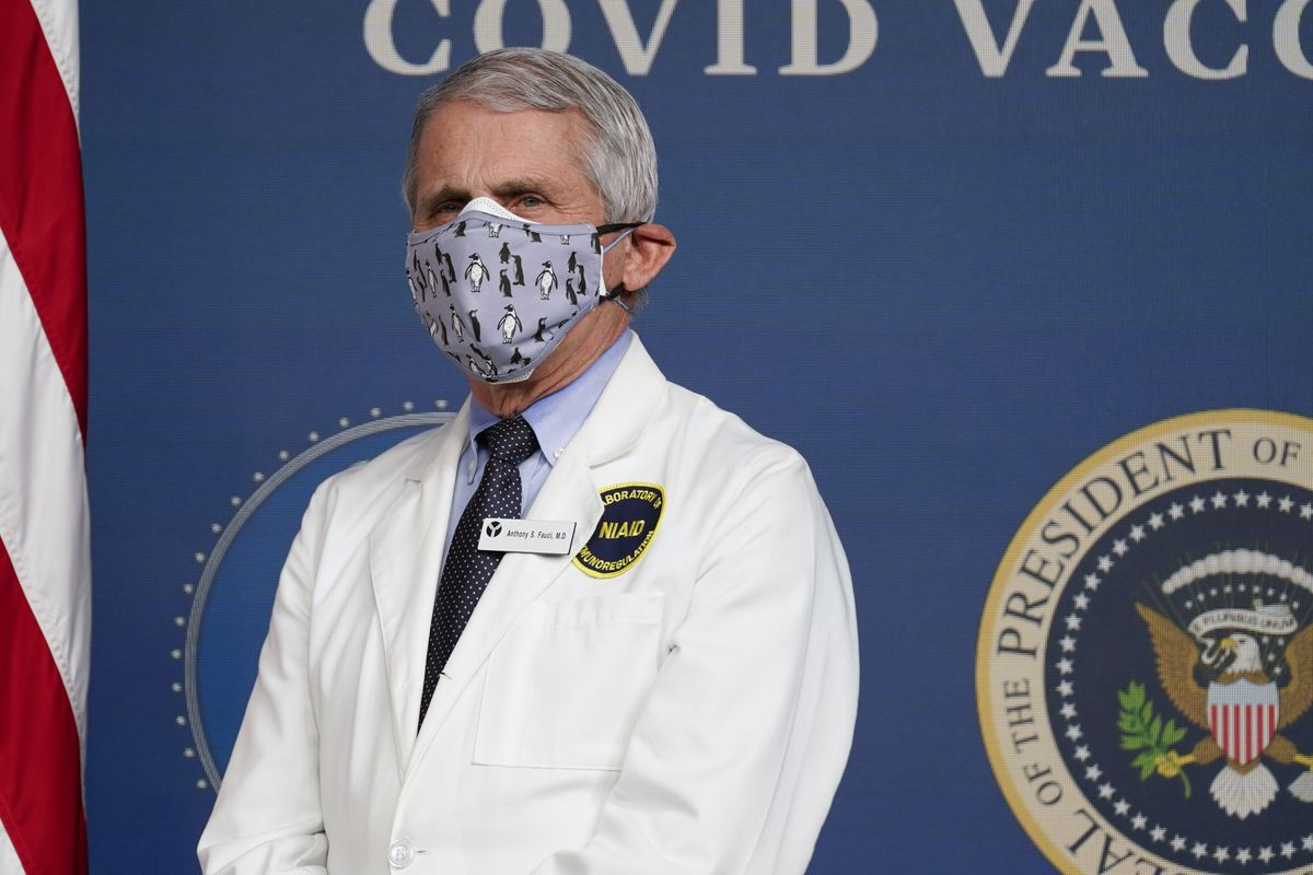 Dr. Anthony Fauci listens as President Joe Biden speaks during an event to commemorate the 50 millionth COVID-19 shot in Washington.