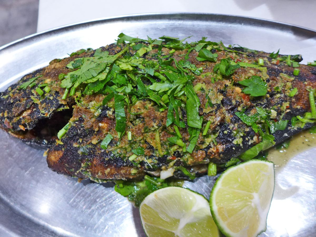 A blackened whole fish covered with parsley on a silver salver.