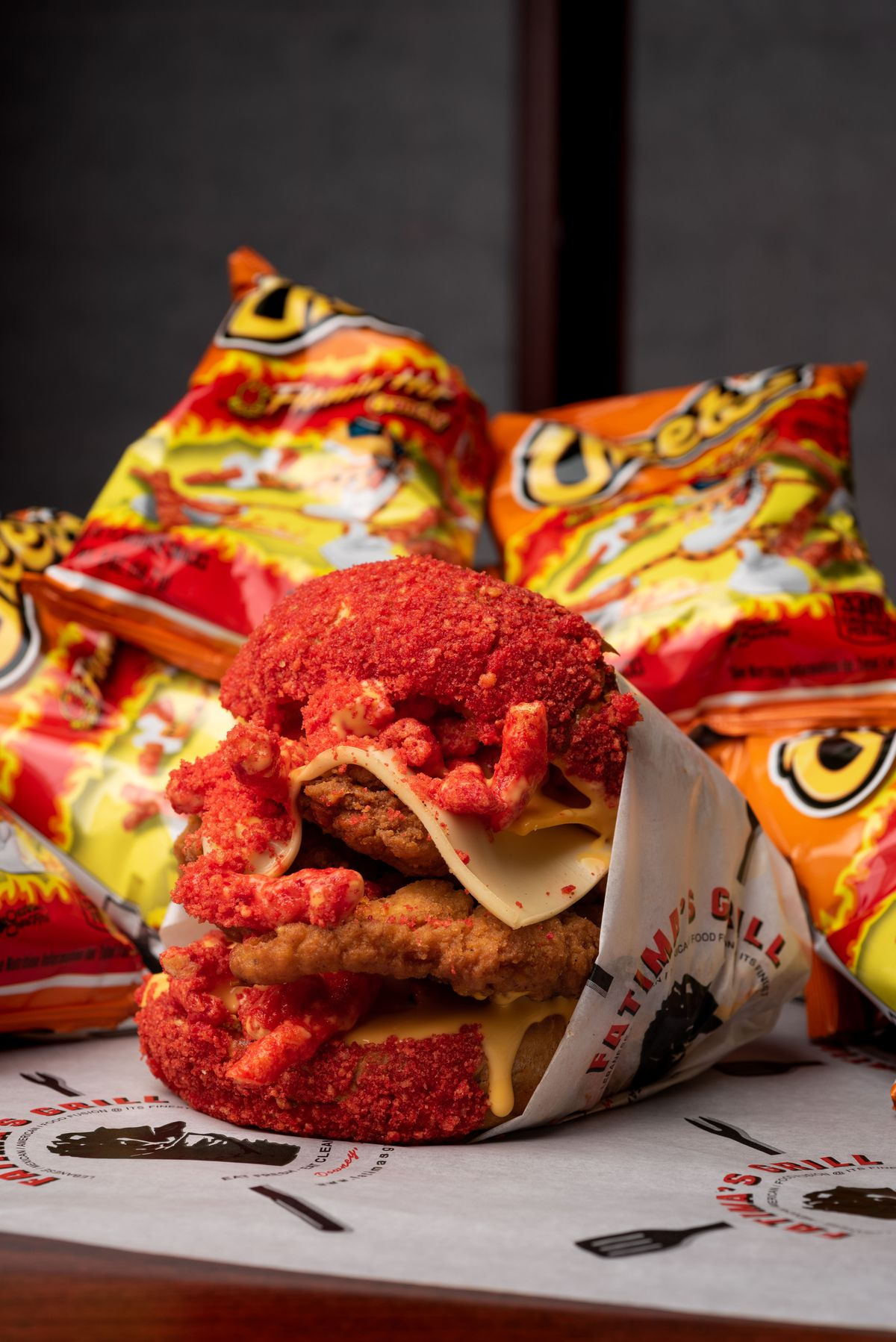 Hot Cheetos crust onto a bun and fried chicken sandwich, with more Hot Cheetos bag in the back.