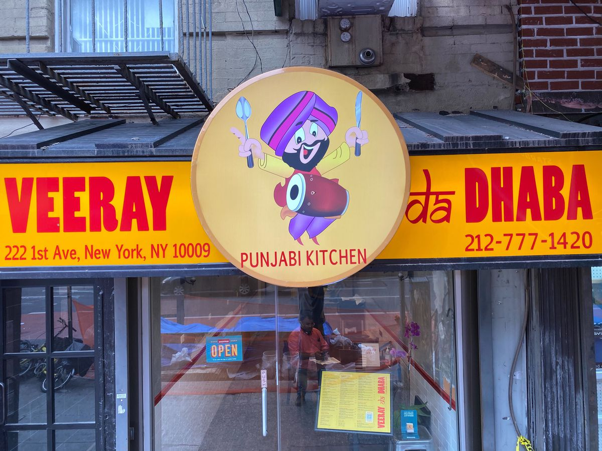 """The front of the restaurant with a menu hanging in the window and a big yellow sign with red lettering that reads """"Veeray da Dhaba"""""""
