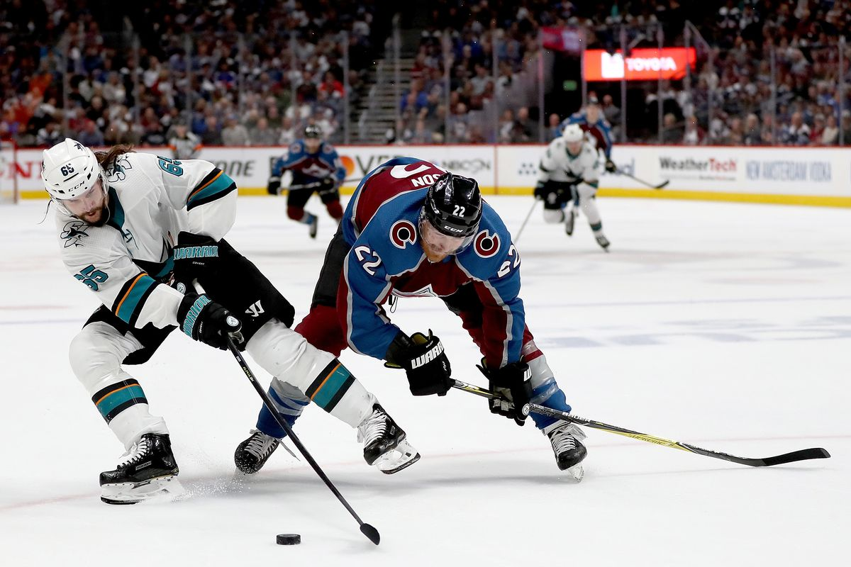 Erik Karlsson of the San Jose Sharks fights for the puck against Colin Wilson of the Colorado Avalanche in the second period during Game 6 of the Western Conference Second Round during the 2019 NHL Stanley Cup Playoffs at the Pepsi Center on May 6, 2019 i