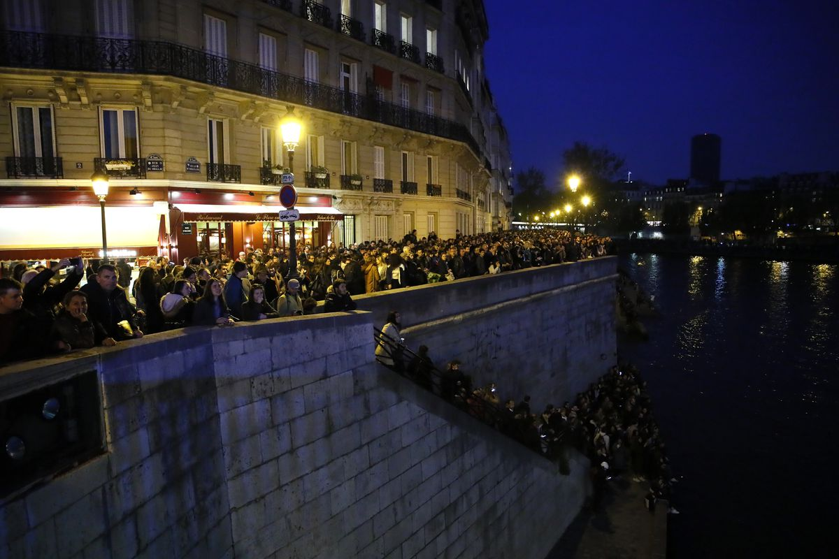 People watch Notre Dame Cathedral burning from the Seine river banks in Paris, Monday, April 15, 2019. A catastrophic fire engulfed the upper reaches of Paris' soaring Notre Dame Cathedral as it was undergoing renovations Monday, threatening one of the gr
