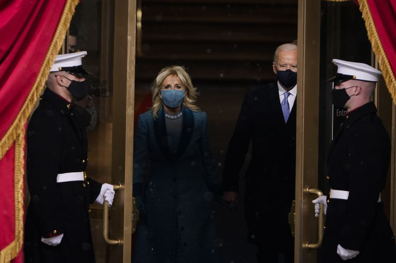 Joe Biden and his wife Jill walk out to the inauguration stage, with guards opening the doors.