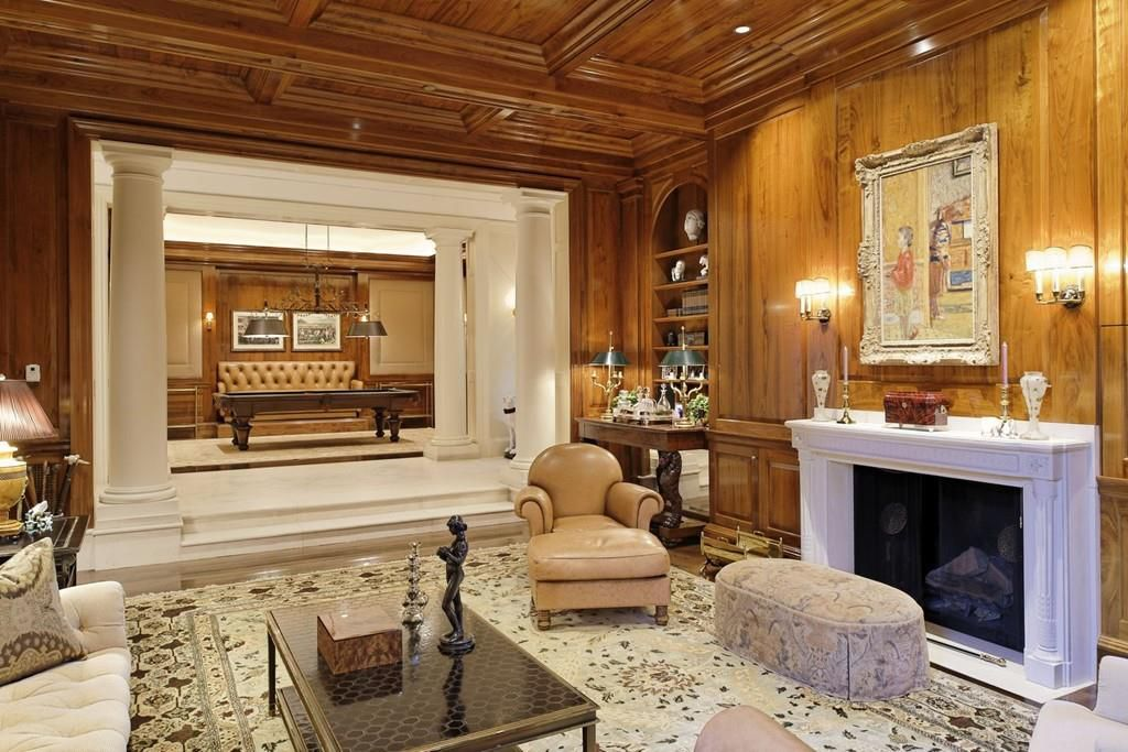 A wood-paneled den with a fireplace and furniture and a large opening leading to a marble entryway.
