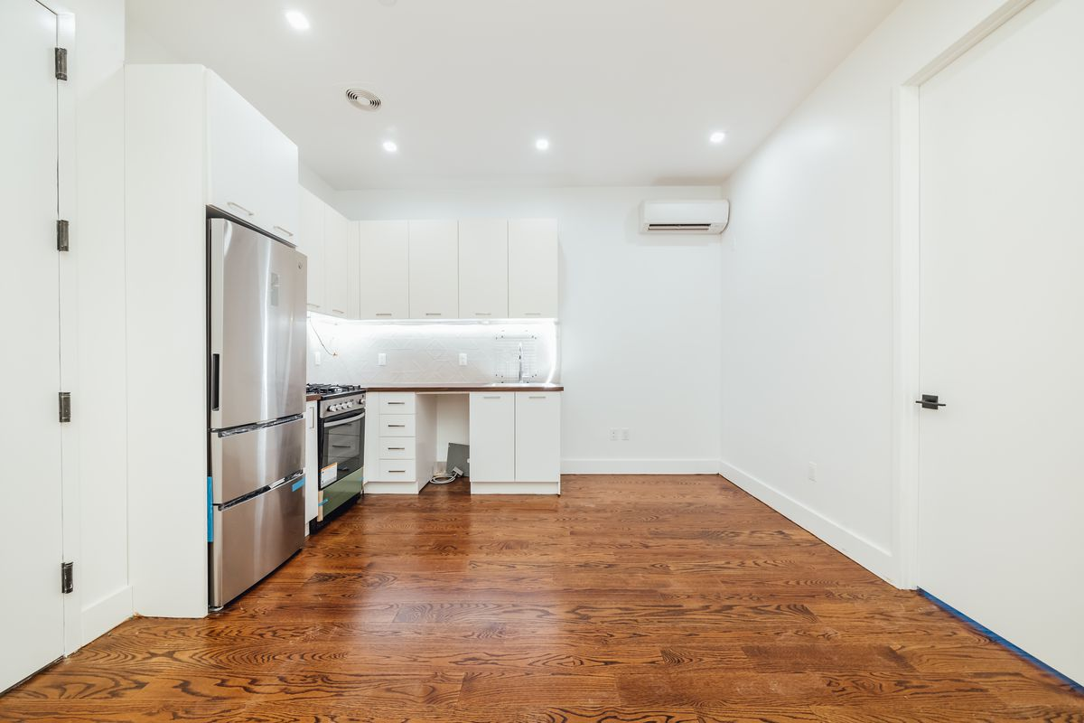A living area with hardwood floors, white walls, and a kitchen with white cabinetry.