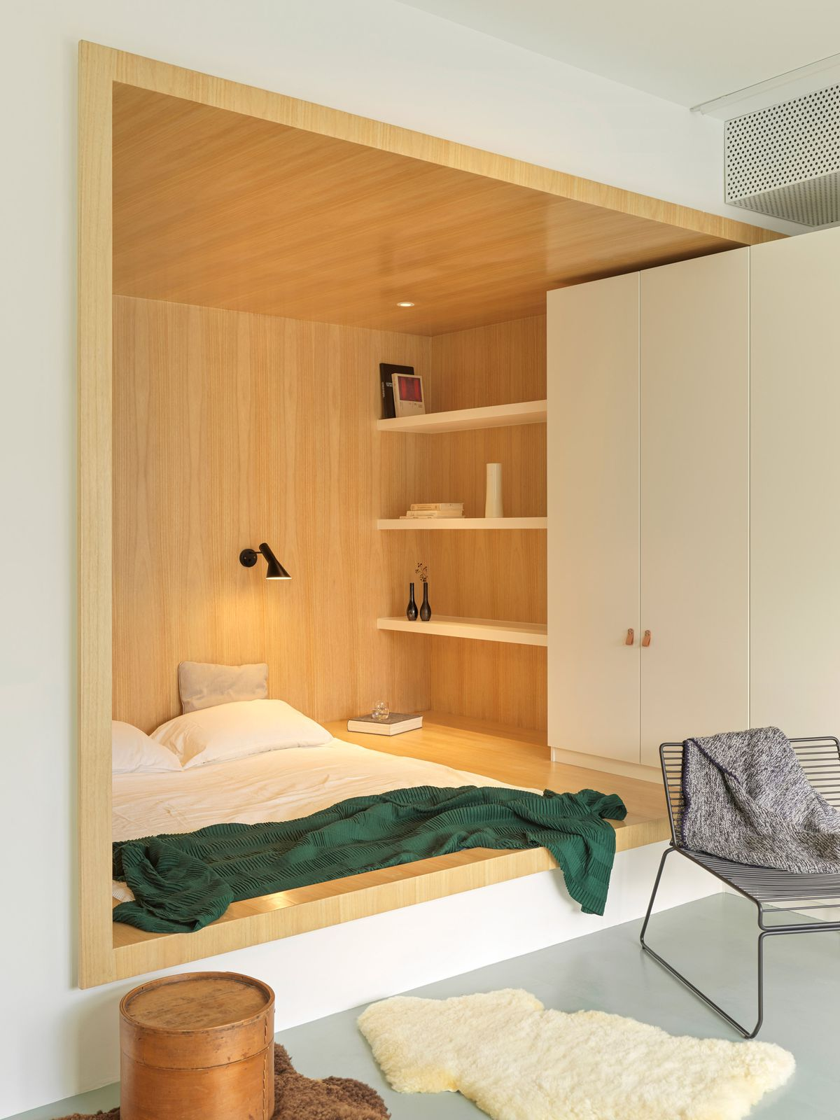 Bed in built-in nook with light timber walls.