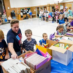 Bridgit LeVie, second from left, and her children, Coen LeVie, 11, Kasen LeVie, 7, Kyland Sawyer, 5, and Aubrey Sawyer, 7, left to right, pick out free school supplies during Operation Homefront's annual Back-to-School Brigade event at Hill Field Elementary on Tuesday, Aug. 13, 2019.
