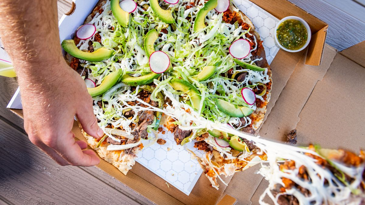 A wide, thin tortilla imported from Oaxaca is the crispy base for Taqueria Xochi tlayudas with beef tenderloin, chorizo, nopales, Oaxaca cheese, refried beans, avocado, and radish