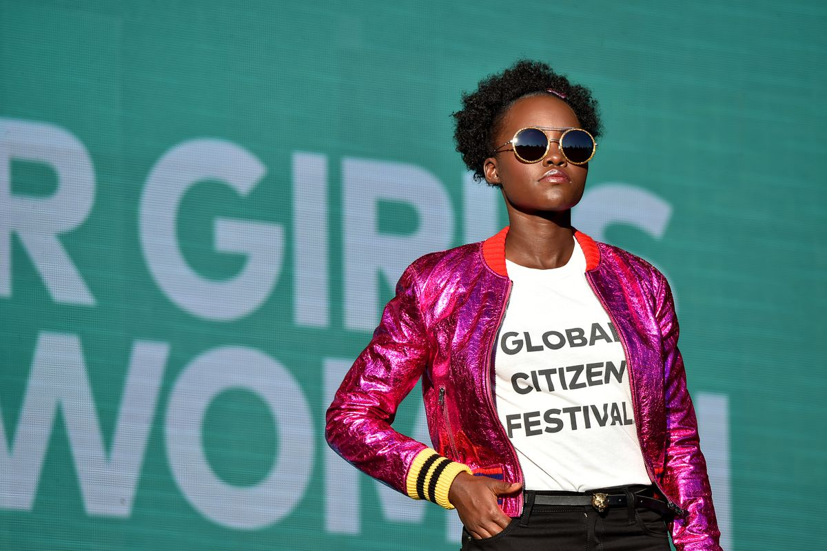 Nyong'o wears a white t-shirt and a sparkly hot pink bomber jacket.
