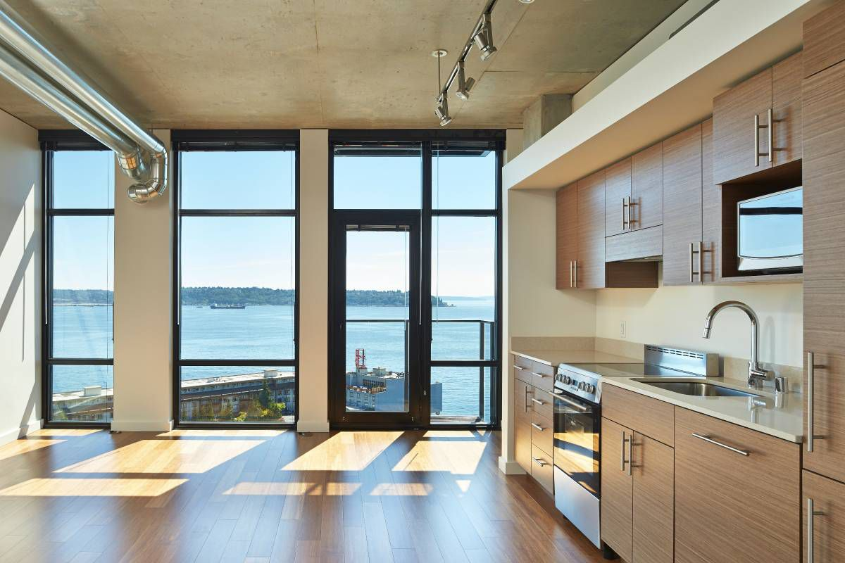 An empty loft with a water view. Kitchen runs along the wall to the right.