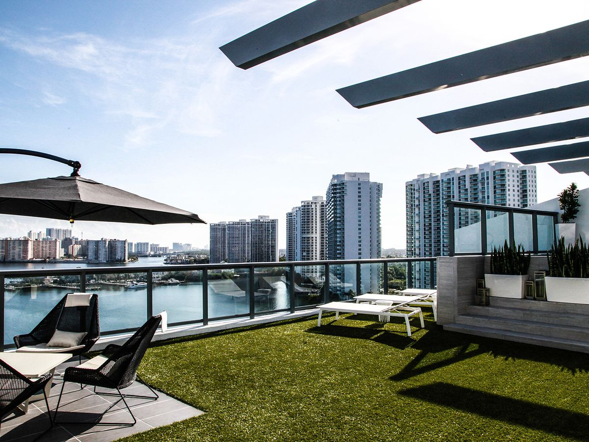 A rooftop terrace with turf and a plunge pool in addition to contemporary furniture in AVentura with the bay in the background