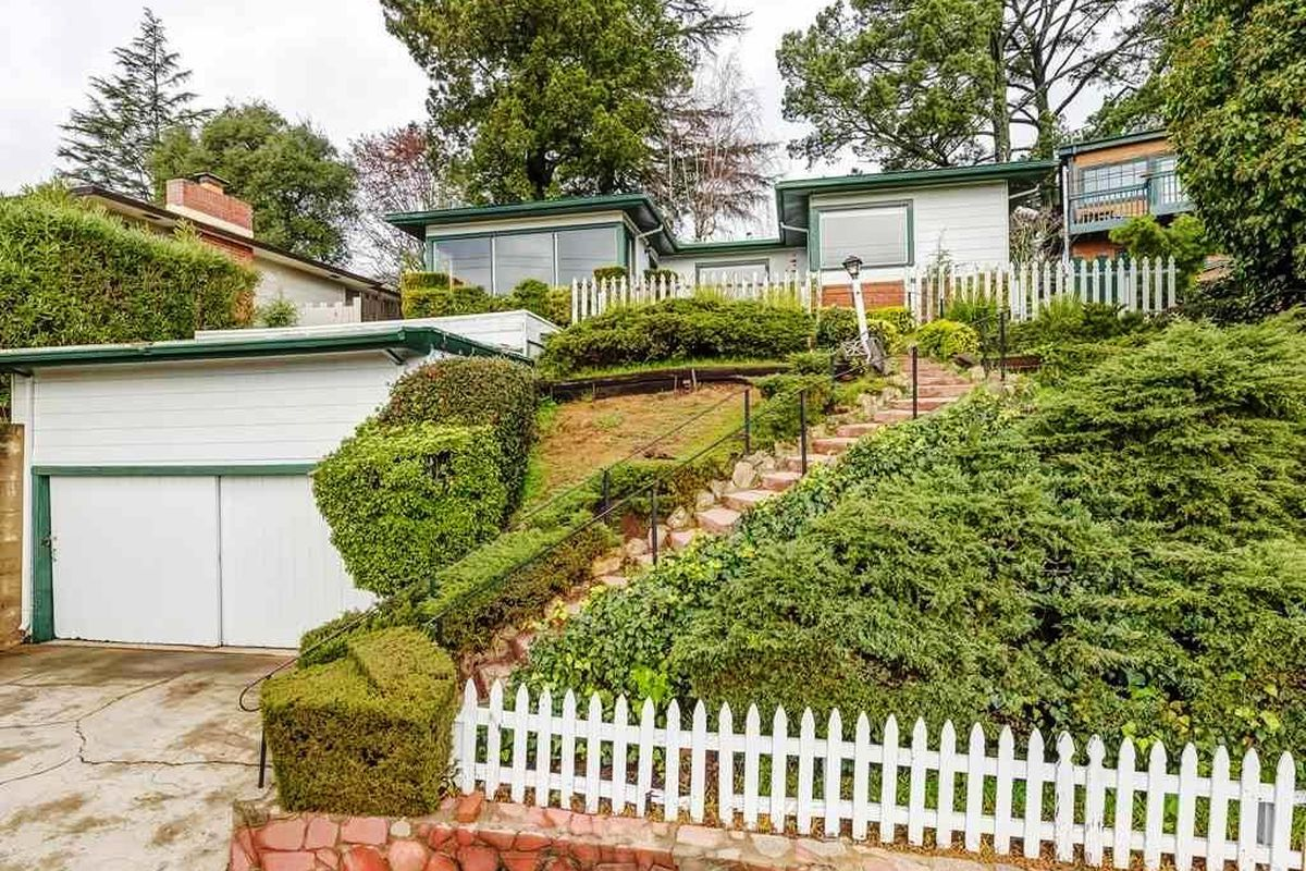 A white and green house at the top of a hill covered in greenery, with a white picket fence.