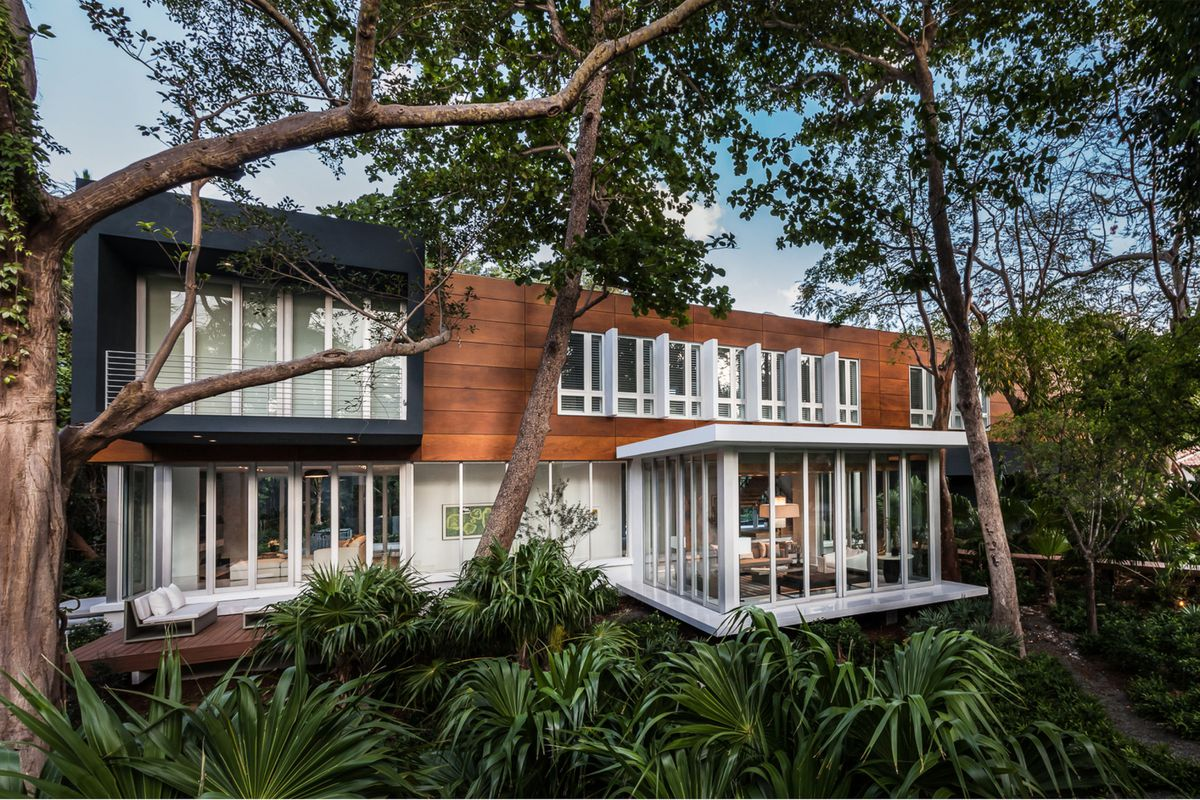 Backyard view of a lush three-toned house (wood colored, blue, and white) engulfed in jungle
