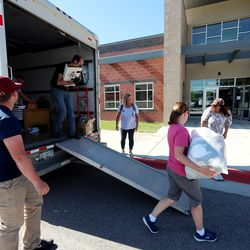 Friends, family and fellow teachers help to unload yard sale items from a truck for a fundraiser for Ravien Parsons at Summit Academy in Bluffdale on Friday, June 19, 2020. Parsons has experienced a sudden disability after being diagnosed with stiff-person syndrome. The charter school where she teaches is holding the fundraiser to help her buy a wheelchair-accessible van so she can continue to work and more effectively live her life.