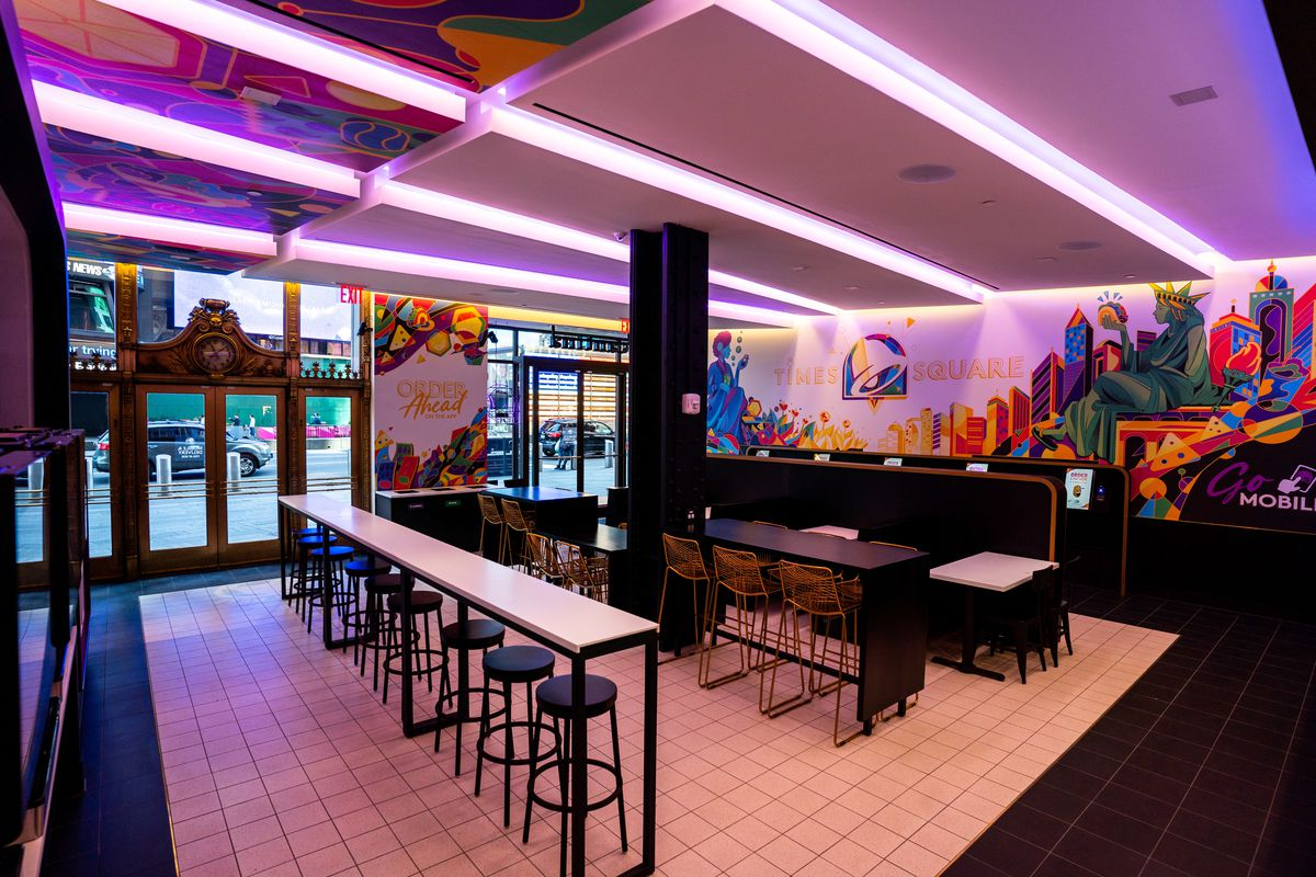 A clubby counter-service restaurant with a handful of stools, tables, chairs, and tile floors appears in purple lighting due to overhead lights
