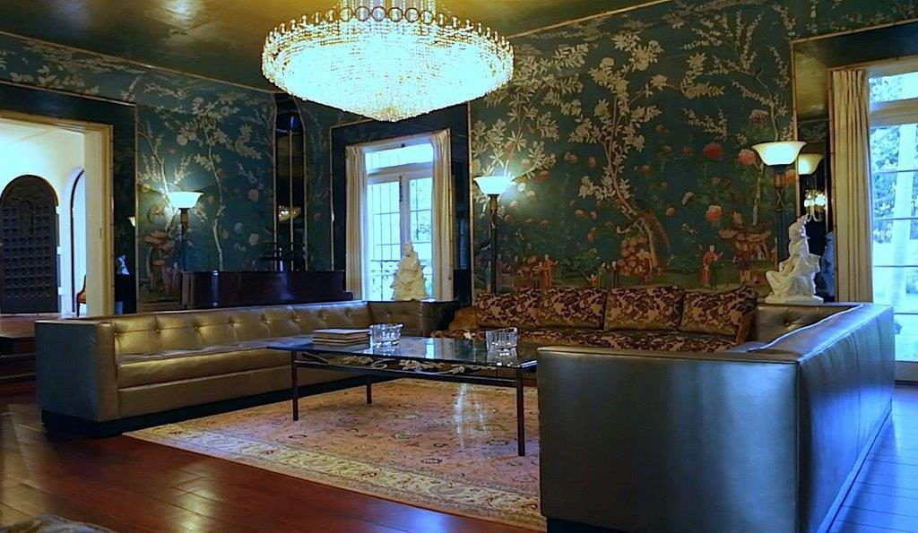 A grand crystal chandelier hangs in a wallpapered room decorated with leather couches.